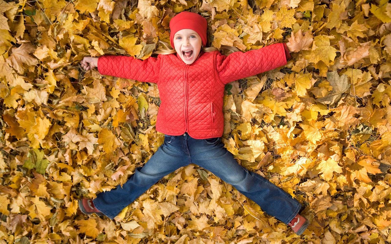 hd-herfst-wallpaper-een-kind-speelt-in-de-herfstbladeren-achtergrond-foto1